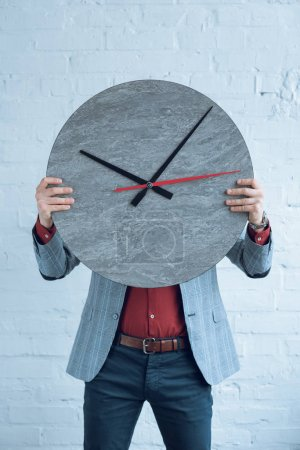 Man holding large clock in front of his face