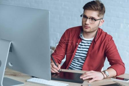 Concentrated freelancer man with graphic tablet sitting by working table