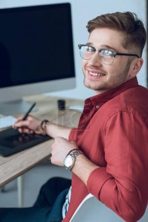 Young smiling man by working table with graphic tablet and computer