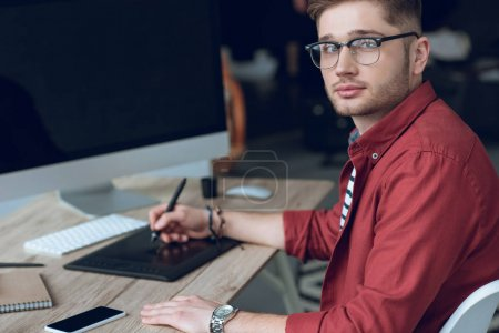 Bearded man sitting by table with computer and graphic tablet