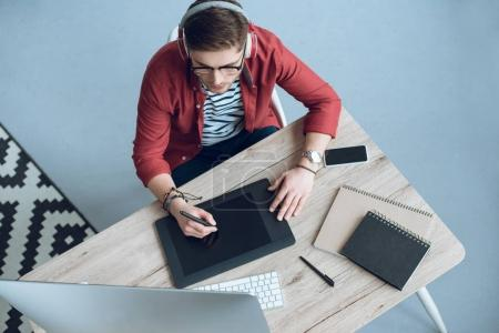 Young man in headphones using graphic tablet by table with computer