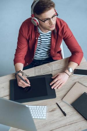 Man freelancer in headphones at work by table with computer and graphic tablet