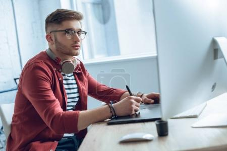 Thoughtful freelancer working by table with graphic tablet