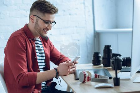 Happy freelancer man using smartphone sitting by working table
