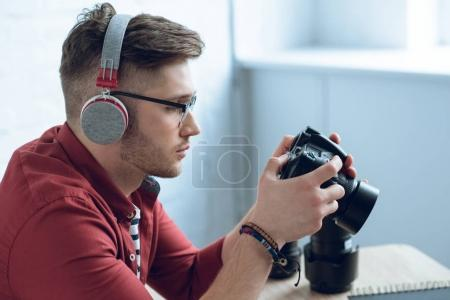 Young bearded man in headphones holding camera by table