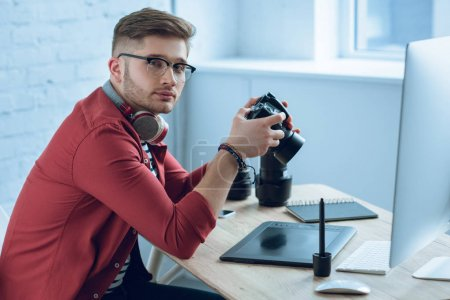 Young photographer holding professional camera by working table