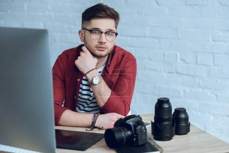 Young bearded man by working table with camera and computer