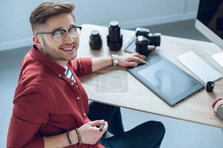 Happy freelancer man sitting by working table with graphic tablet