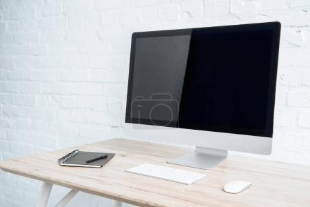 Photo for Blank computer screen with notebook on table in light office - Royalty Free Image