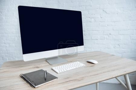 Photo for Computer with notebook on table in light office - Royalty Free Image