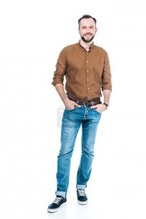 Photo for Full length view of handsome bearded man standing with hands in pockets and smiling at camera isolated on white - Royalty Free Image