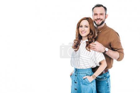 schönes glückliches Paar, das zusammen steht und in die Kamera lächelt, isoliert auf weiß