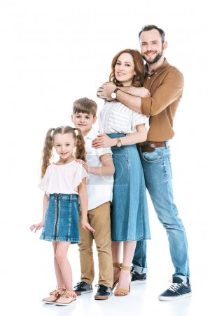 vue pleine longueur de la famille heureuse avec deux enfants debout ensemble et souriant à la caméra isolée sur blanc