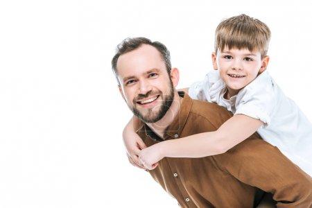 Photo pour Heureux père piggybackking petit fils et souriant à la caméra isolé sur blanc - image libre de droit