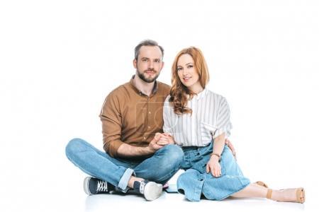 Foto de Hermosa pareja feliz sentados juntos, tomados de la mano y sonriendo a cámara aislada en blanco - Imagen libre de derechos