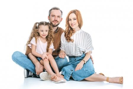 happy family with one child sitting together and smiling at camera isolated on white