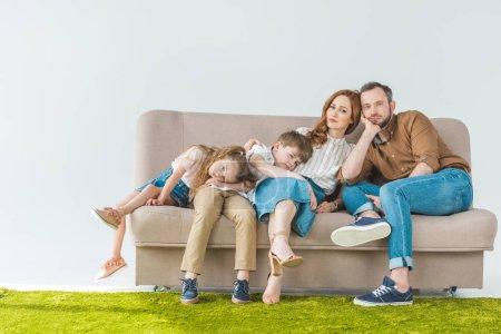 famille avec deux enfants reposant sur le canapé et regarder la caméra sur fond gris