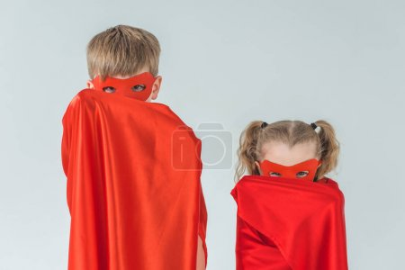 children in masks covering faces with cloaks and looking at camera isolated on grey