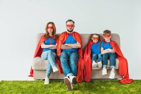 Photo for Family in superhero costumes sitting with crossed arms and looking at camera on grey - Royalty Free Image