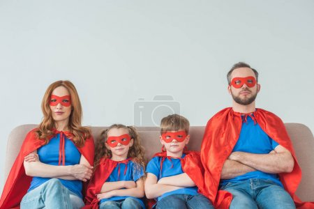 Photo for Super family in masks and cloaks sitting with crossed arms and looking at camera on grey - Royalty Free Image