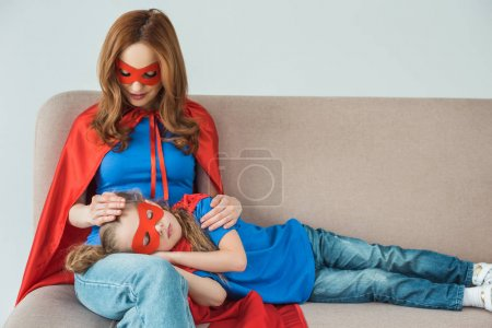 Photo for Super mother in mask and cloak looking at little daughter sleeping on her knees on sofa - Royalty Free Image