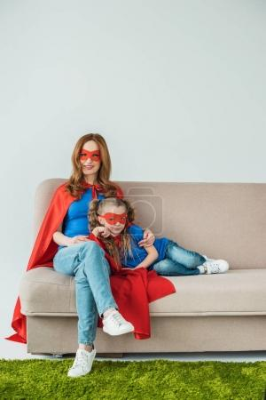 super mother and daughter in masks and cloaks sitting on sofa and smiling at camera