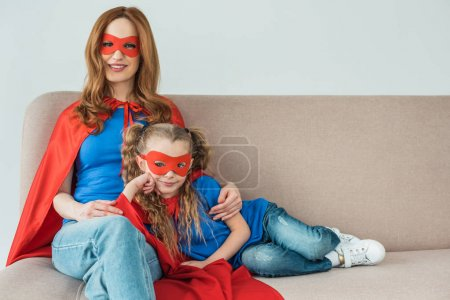 happy mother and daughter in superhero costumes sitting on sofa and smiling at camera