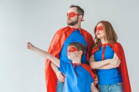 Foto de Familia de superhéroes en máscaras y mantos de pie juntos y mirando a aislaron en gris - Imagen libre de derechos