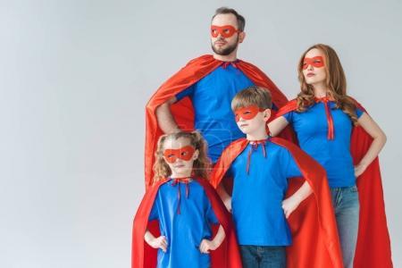 Foto de Familia de superhéroes trajes de pie con las manos en la cintura y mirando lejos aislado en gris - Imagen libre de derechos