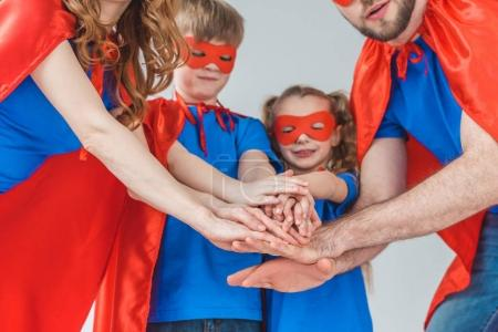 cropped shot of super family in costumes stacking hands together isolated on grey