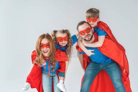 Foto de Super padres piggybacking niños fingiendo ser superhéroes aislados en gris - Imagen libre de derechos