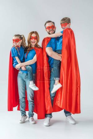 cheerful family of superheroes smiling at camera on grey