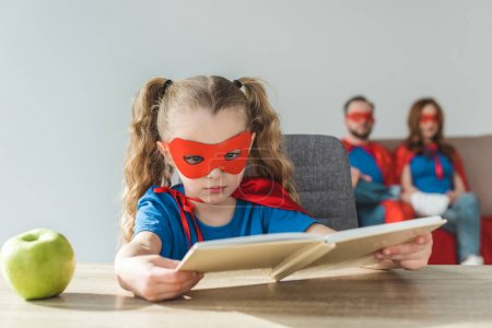 girl in superhero costume reading book while super parents sitting behind