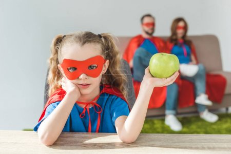 Photo for Girl in superhero costume holding apple and looking at camera while super parents sitting behind - Royalty Free Image