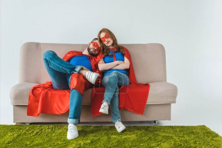 tired couple in superhero costumes sleeping while sitting on sofa on grey