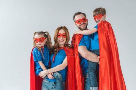 Foto de Familia alegre de superhéroes en máscaras y mantos sonriendo a cámara en gris - Imagen libre de derechos