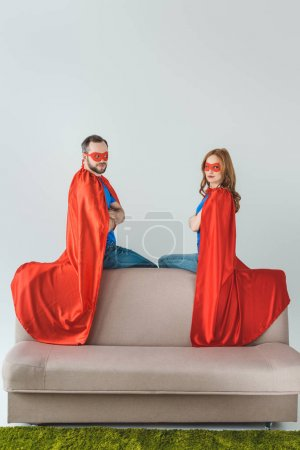 super couple in masks and cloaks sitting on sofa and looking at camera