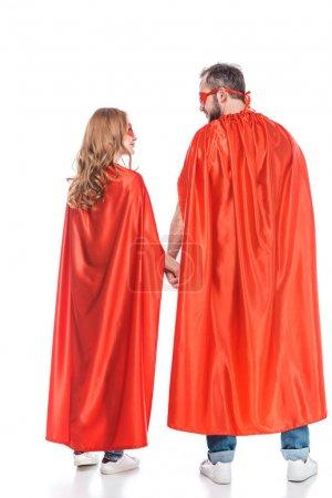 Foto de Vista trasera del par en máscaras y mantos cogidos de la mano y mirando el uno al otro aislado en blanco - Imagen libre de derechos