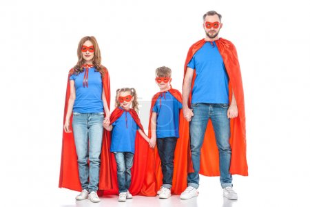 Photo for Super family in masks and cloaks holding hands and looking at camera isolated on white - Royalty Free Image