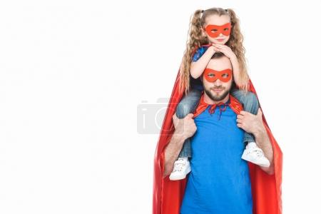 super father carrying little daughter in mask and cloak and looking at camera isolated on white