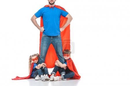 Photo pour Photo recadrée de super papa debout avec les mains sur la taille tout en enfants serrant ses jambes isolés sur blanc - image libre de droit