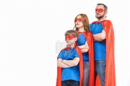 Foto de Super familia de máscaras y capas de pie con los brazos cruzados y mirando lejos, aislados en blanco - Imagen libre de derechos