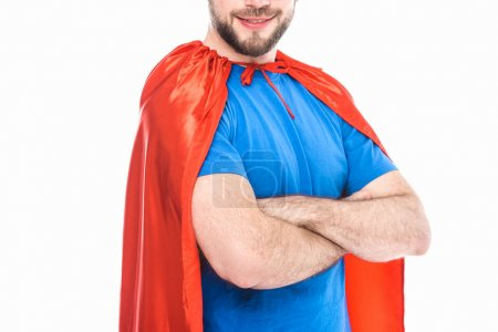 cropped shot of smiling man in superhero costume standing with crossed arms isolated on white