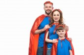 happy family in superhero costumes standing together and smiling at camera isolated on white