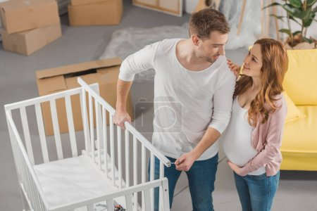 high angle view of happy young pregnant couple smiling each other while standing near baby bed