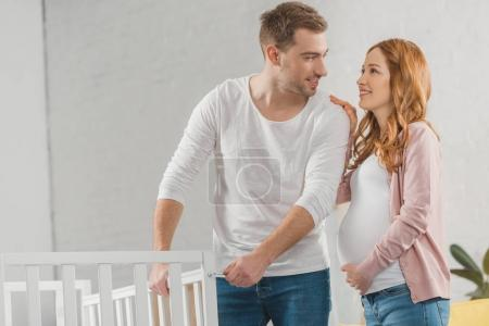 happy young pregnant couple smiling each other while standing near baby bed