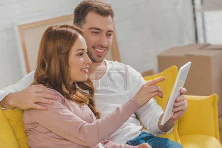 happy young couple using digital tablet during relocation