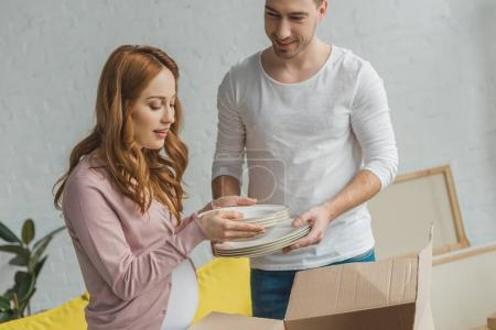 Photo for Young pregnant couple packing plates in cardboard box during relocation - Royalty Free Image