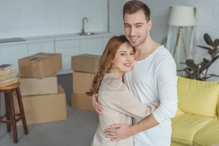 happy young couple hugging and smiling at camera during relocation