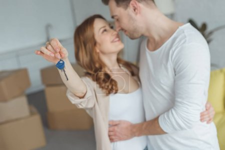 happy young couple holding key from new apartment and smiling each other